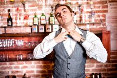 Portrait of angry and stressed barman with bowtie behind the bar. With alcoholic drinks around. Stressful lifestyle of barista concept Stock Photo