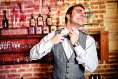 Portrait of angry and stressed bartender or barman with bowtie. Behind the bar with alcoholic drinks around. Stressful lifestyle of barista concept Stock Images