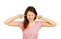 Portrait of angry stressed out young woman plugging ears with fingers and closing eyes tight. emotional girl isolated on white bac stock image