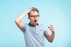 Portrait of angry student young man yelling and screaming on blue background.  Royalty Free Stock Photography