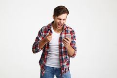 Portrait of an angry unsatisfied man looking at mobile phone. And yelling isolated over white background Royalty Free Stock Image