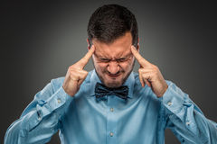 Portrait angry upset young man in blue shirt, butterfly tie Royalty Free Stock Photography
