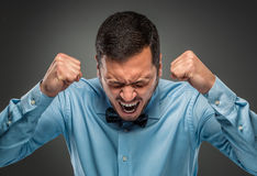 Portrait angry upset young man in blue shirt, butterfly tie Stock Photos