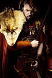 Portrait of angry viking warrior with leather, fur and sword, bo Stock Image