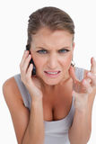 Portrait of an angry woman making a phone call. Against a white background Royalty Free Stock Photos