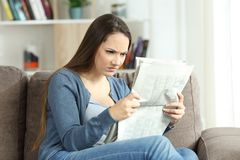 Angry woman reading a newspaper on a couch. Portrait of an angry woman reading bad news in a newspaper sitting on a couch in the living room at home Royalty Free Stock Images