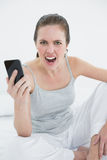 Portrait of an angry woman shouting with mobile phone in hand Stock Photos