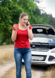 Portrait of angry woman standing at broken car and talking by mo Royalty Free Stock Images