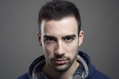 Portrait of angry young bearded male wearing hoodie staring at camera Royalty Free Stock Photography