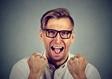 Portrait angry young man screaming. Angry young man in glasses screaming Royalty Free Stock Image