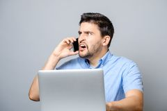 Portrait of angry young man screaming on his mobile phone. Over gray background Stock Photo