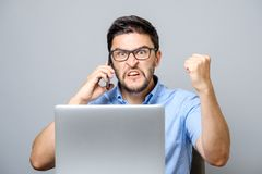 Portrait of angry young man screaming on his mobile phone. Over gray background Royalty Free Stock Photography