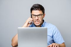 Portrait of angry young man screaming on his mobile phone. Over gray background Royalty Free Stock Photo