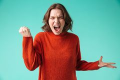 Portrait of an angry young woman dressed in sweater. Screaming isolated over blue background Royalty Free Stock Photos
