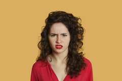 Portrait of angry young woman frowning over colored background Royalty Free Stock Image