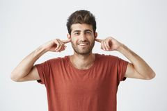 Portrait of annoyed young male Caucasian with eyes closed plugging his ears with fingers can`t stand loud noise or. Ignoring stressful unpleasant situation or Royalty Free Stock Photos