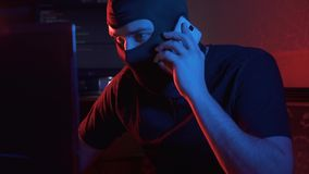 An anonymous man in a balaclava communicates by phone. Portrait of an anonymous man in a balaclava at acomputer types concept idea stock video