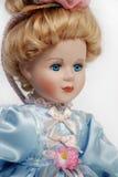 Portrait of antique porcelain doll face. Portrait of retro porcelain doll face with blue dress Royalty Free Stock Images