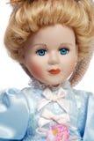 Portrait of antique porcelain doll face. Portrait of retro porcelain doll face with blue dress Stock Photo