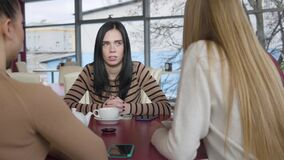 Portrait of anxious serious Caucasian woman talking with friends in cafe. Brunette young woman sitting with fellows in
