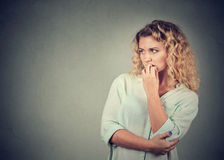 Portrait anxious woman biting her fingernails craving for something. Isolated on gray background. Negative human emotions royalty free stock photography