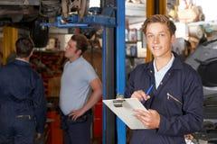 Portrait Of Apprentice Mechanic Holding Clipboard Working In Auto Repair Shop stock photo
