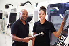 Portrait Of Apprentice Working With Engineer On CNC Machine Stock Photography