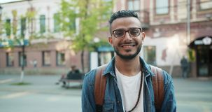 Portrait of Arabian bearded guy wearing trendy clothing and beads outdoors. Portrait of Arabian bearded guy wearing trendy clothing and beads standing outdoors stock video footage