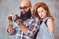 Portrait of an Arabian bearded male holding a camera and his beautiful redhead girlfriend. stock images