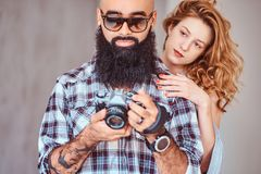 Portrait of an Arabian bearded male holding a camera and his beautiful redhead girlfriend. royalty free stock images