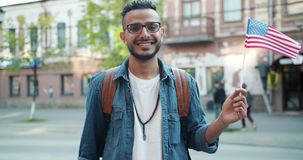 Portrait of Arabian student holding American flag in the street smiling. Portrait of happy Arabian student holding American flag in the street smiling looking at stock footage