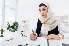 Portrait of arabic businesswoman looking at camera while signing papers. At workplace Stock Photos