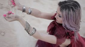 Portrait in Arabic style. Beautiful woman pours sand from hands. stock footage