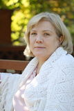Portrait in an arbour. Middle age blonde woman in autumn garden Stock Photo