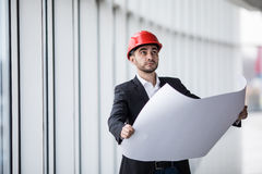 Portrait of an architect builder studying layout plan of the building, serious civil engineer working with documents on Royalty Free Stock Images