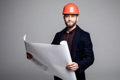 Portrait of an architect builder studying layout plan of the rooms, serious civil engineer working with documents on construction Royalty Free Stock Photography