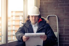 Portrait of an architect builder studying layout plans of building. Soft focus, toned. stock photo