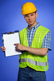 Portrait of architect in coveralls and hardhat pointing at clipboard Royalty Free Stock Photography