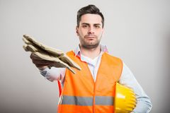 Portrait of architect handing pair of working gloves Stock Image
