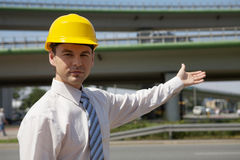 Portrait of architect in hardhat gesturing at construction site Royalty Free Stock Images