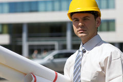 Portrait of architect in hardhat holding blueprint at construction site Stock Photo