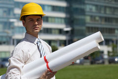 Portrait of architect in hardhat holding blueprint at construction site Royalty Free Stock Photos