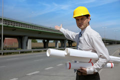 Portrait of architect in hardhat holding blueprint and gesturing Royalty Free Stock Image
