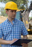 Portrait of architect holding clipboard at construction site Stock Photo