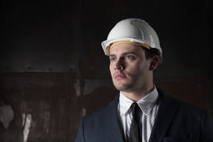 Portrait of a architect in industrial concept in white helmet on dark background Royalty Free Stock Images