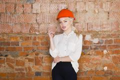 Portrait of architect student or painter with blueprints protect helmet wearing. Brick red background. Portrait of architect student woman with blueprints Royalty Free Stock Images