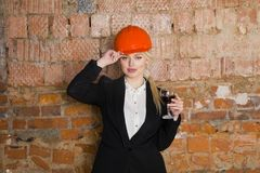 Portrait of architect student or painter with glass of wine and protect helmet wearing. Brick red background. Portrait of architect student woman with Royalty Free Stock Photo