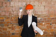 Portrait of architect student or painter with glass of wine and protect helmet wearing. Brick red background. Portrait of architect student woman with Royalty Free Stock Images