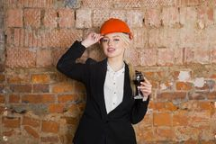 Portrait of architect student or painter with glass of wine and protect helmet wearing. Brick red background. Portrait of architect student woman with Stock Photos