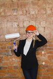 Portrait of architect student or painter with paint roller and protect helmet wearing. Brick red background. Portrait of architect student or painter with paint Royalty Free Stock Photos